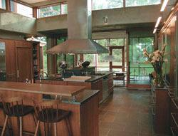 A one-story kitchen separates the house's public and private sections.